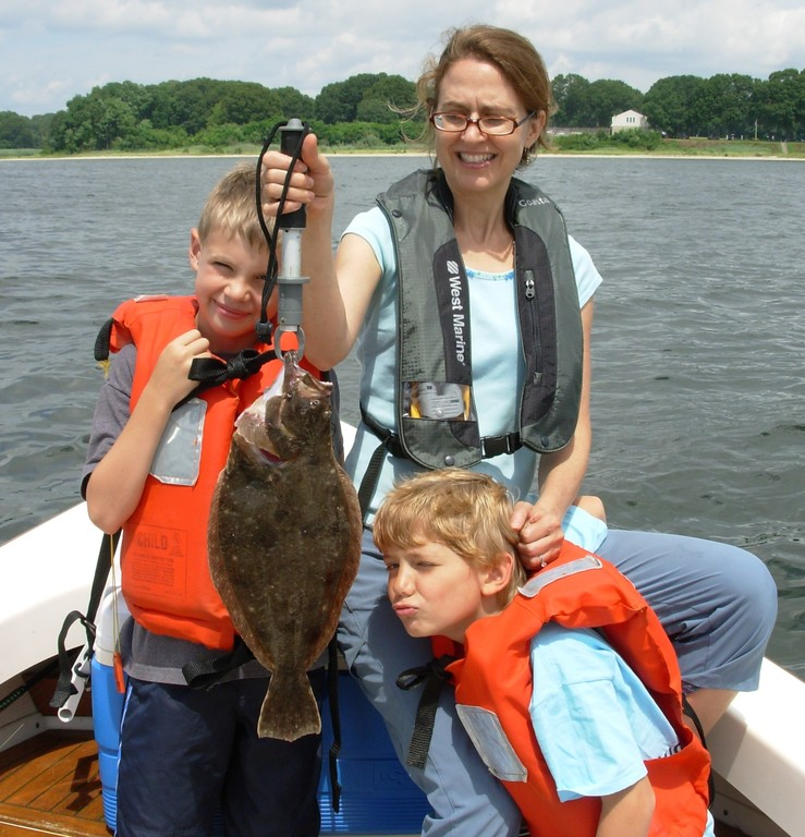 Fluke fishing:  Lorna Russell of Providence with the fluke she caught off the Beavertail area of Jamestown. Her son Liam (right) and friend Mathew look on.