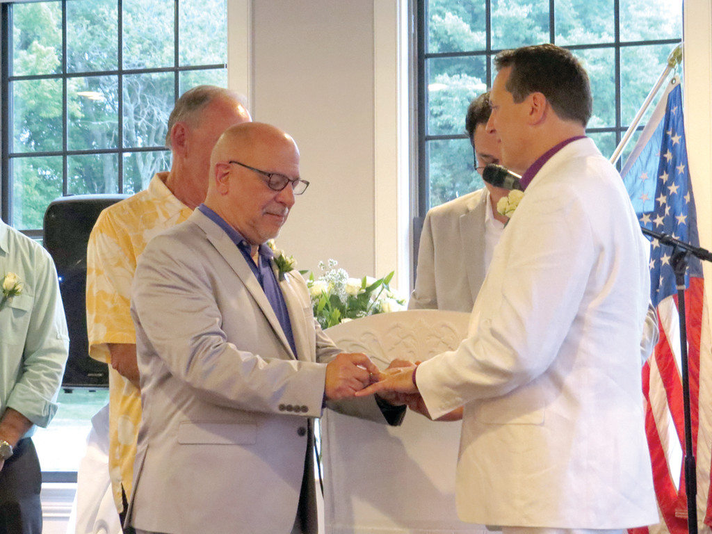 LAWFULLY WEDDED SPOUSE: Anthony Caparco happily places Ferri's diamond-studded wedding band on his ring finger during the couple's marriage ceremony, which was officiated by House Speaker Gordon Fox.