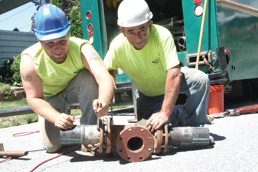 JUST IN CASE: Chris Polak Jr., a laborer with Rosciti, and foreman John Monteiro put the finishing touches to a temporary fire hydrant before installing it on Bluff Avenue in Cranston.