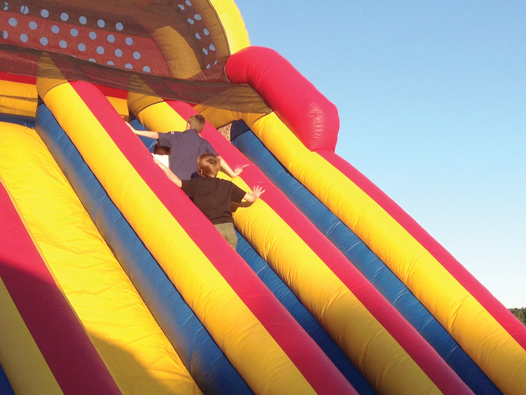 BOUNCING AROUND: Children as they climb up the bouncy slide and prepare to go down.