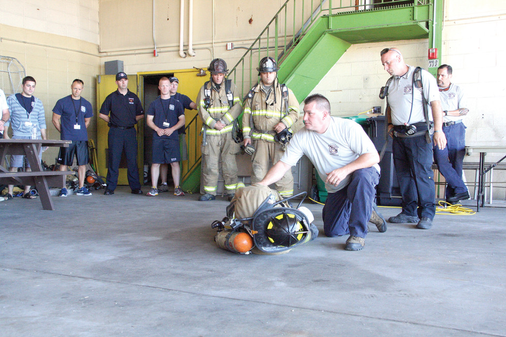 DEMONSTRATING A RESCUE: New York City firefighter Ray Griffin, one of several instructors from P. L. Vulcan Fire Training Concepts, demonstrates how he would pull a downed firefighter from a burning building.
