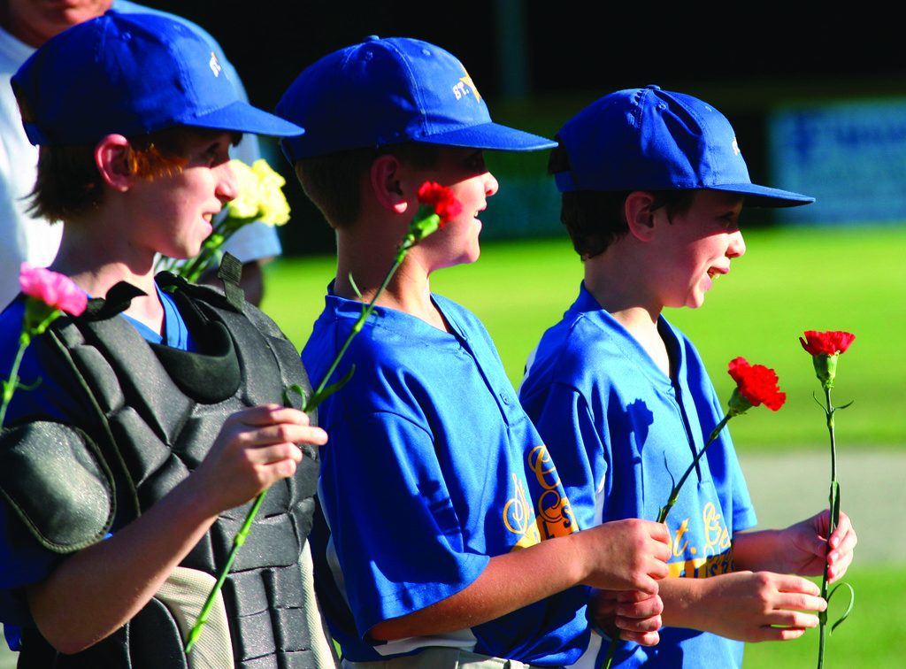 TAKING IT IN: St. Greg's players hold on to their flowers before the game.