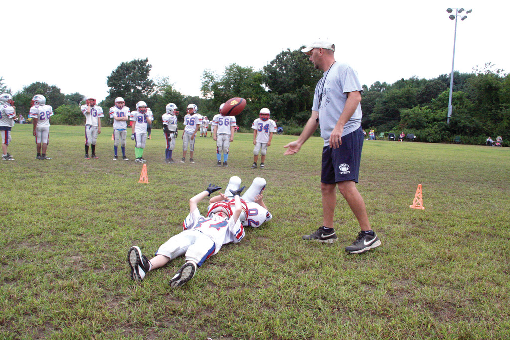 Junior Pee Wee coach Jesse Babcock runs a drill during practice.