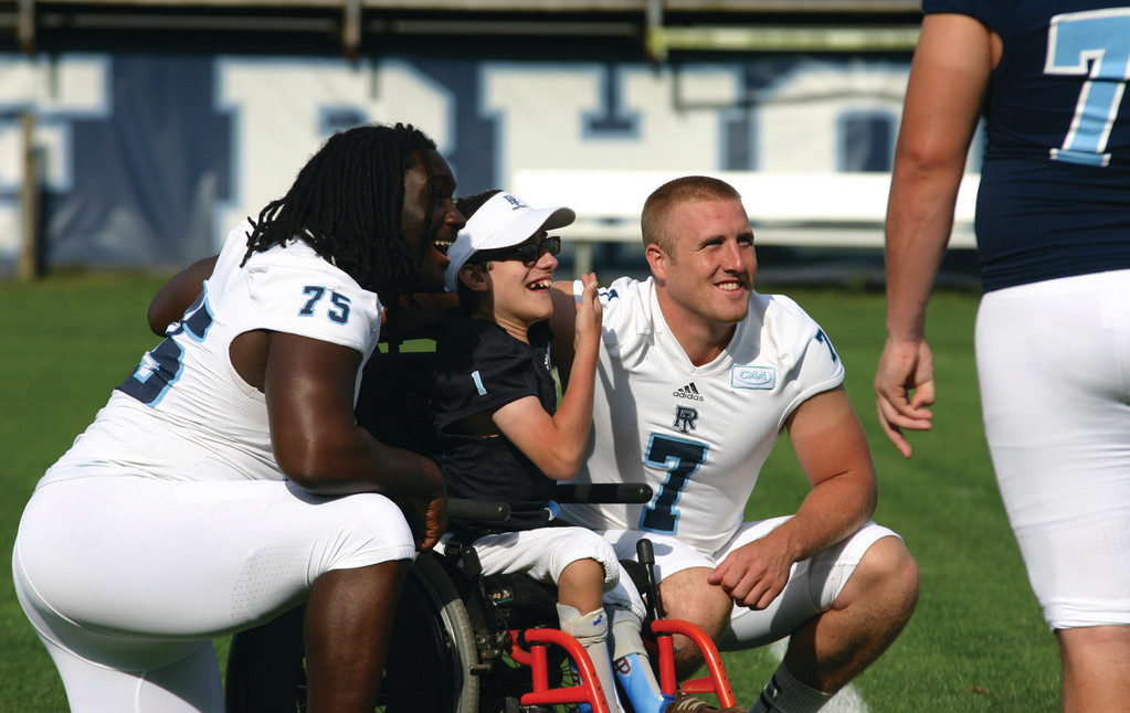ALL SMILES: Evan Huddon poses for a picture with URI's Andrew Belizaire (left) and quarterback Bob Bentsen.