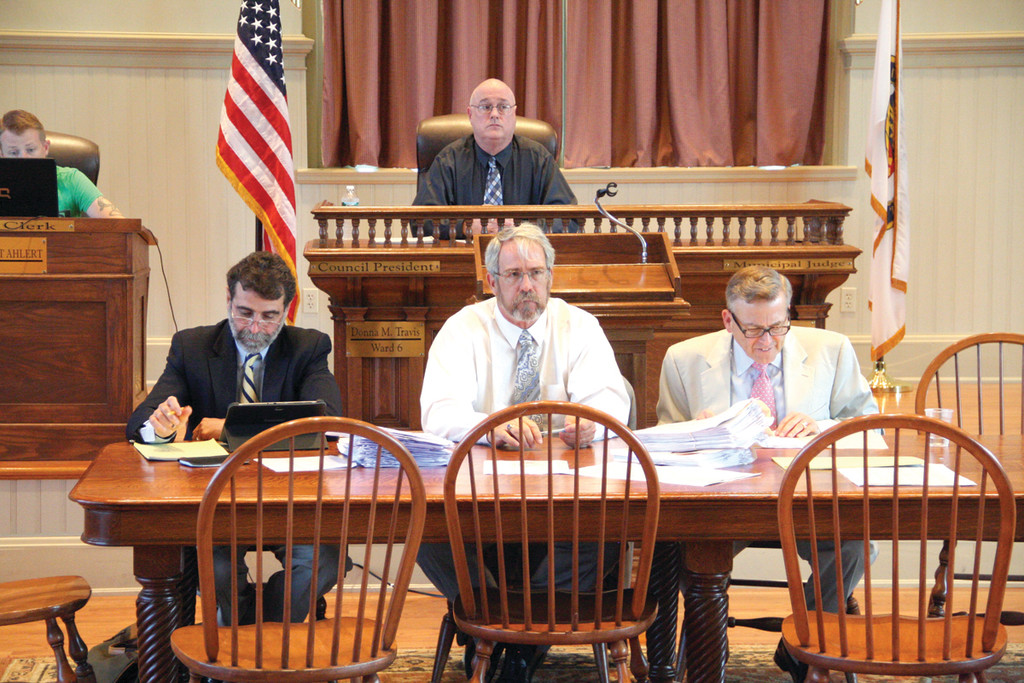 BEST SEAT IN THE HOUSE: Joseph Cavanaugh looks down from his position as spotter at Friday's tax sale being conducted by Peter Ruggiero, Ken Mallette and David Olsen in front of him.