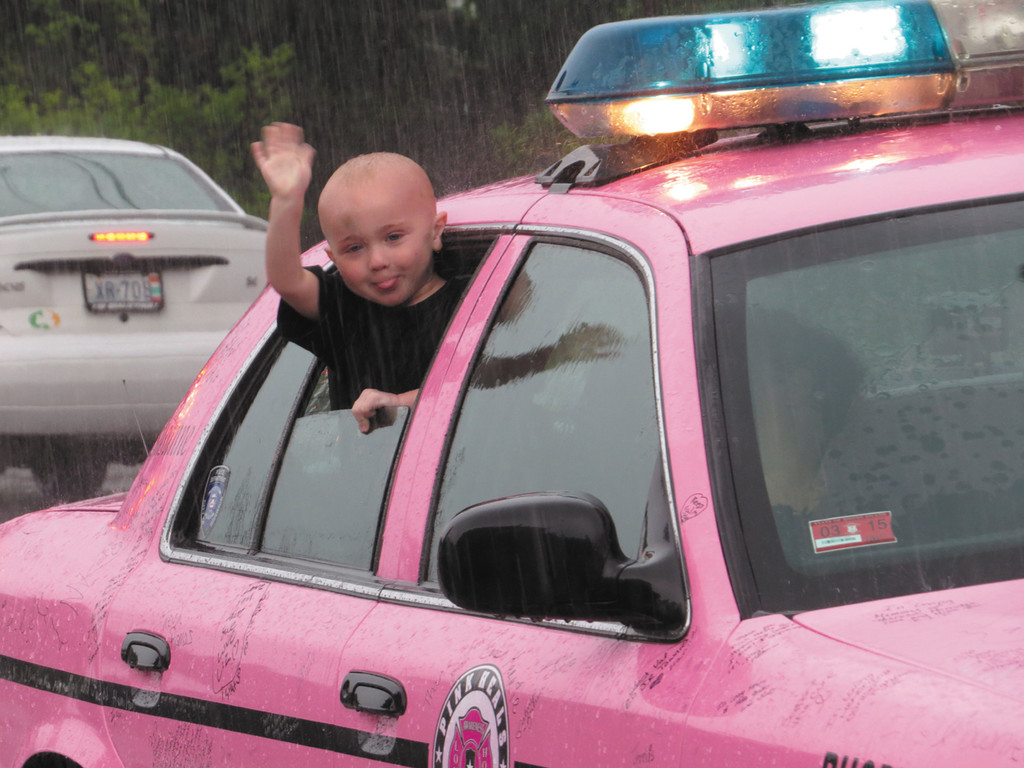 WITH A SMILE AND A WAVE: This little kid had fun sticking his head out of the police car into the rain, waving to anyone who walked by. The National Tour of Pink Heals made a visit to Hasbro Children's Hospital during their time in Rhode Island to visit young kids fighting cancer.