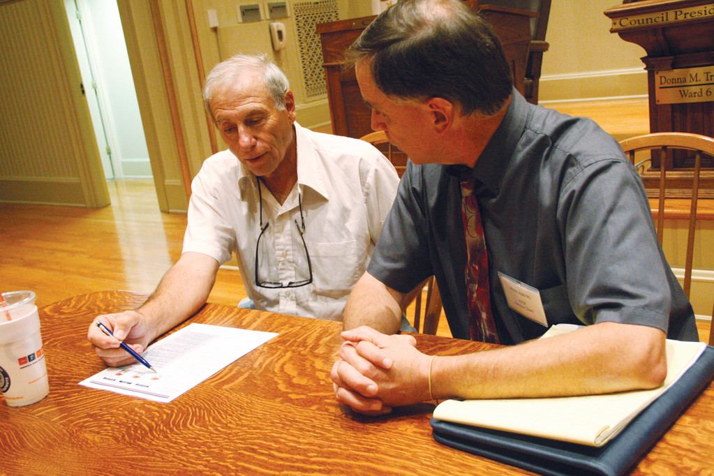 LOOKING FOR OPTIONS: Conimicut property owner Ralph Bozzi (left) talks with Tom Young of the National Flood Insurance Program at the information held last week by the Rhode Island Emergency Management Agency and FEMA.
