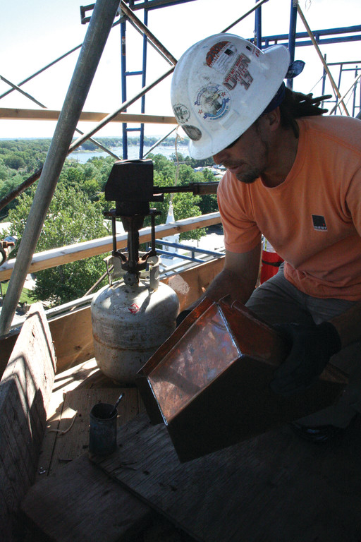 Dave Faria shapes a piece of copper and sodders it before it is affixed to the trim of the tower dome.