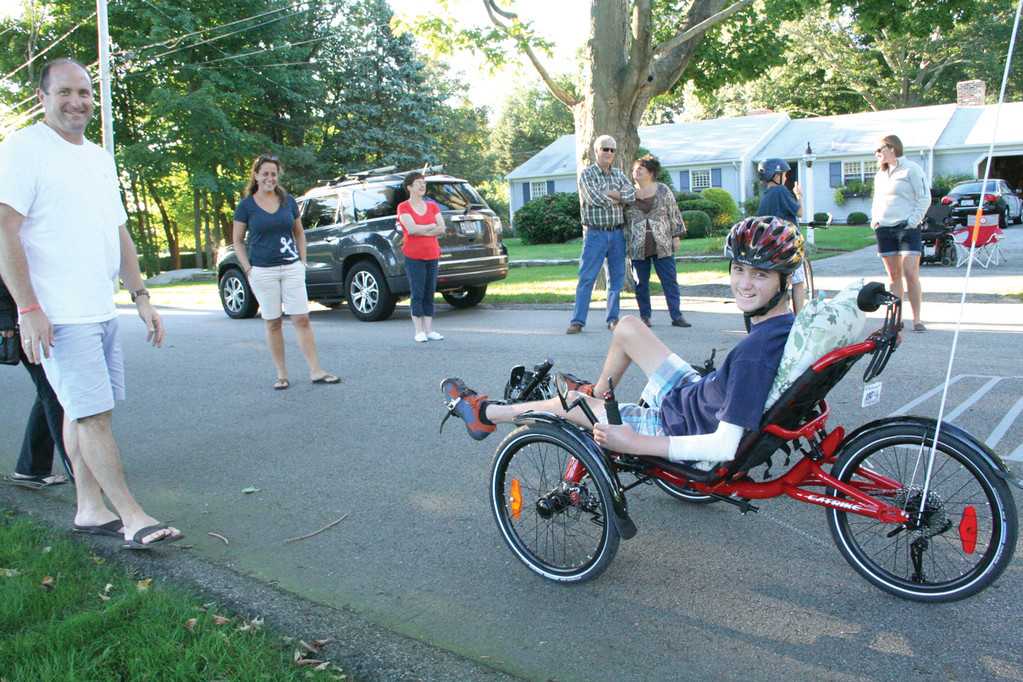 PARTNERS MAKE IT POSSIBLE: Andrew Martin and his new wheels with Lauren Lichtenauer, founder of Christopher�s Promise, family and neighbors in front of his home.
