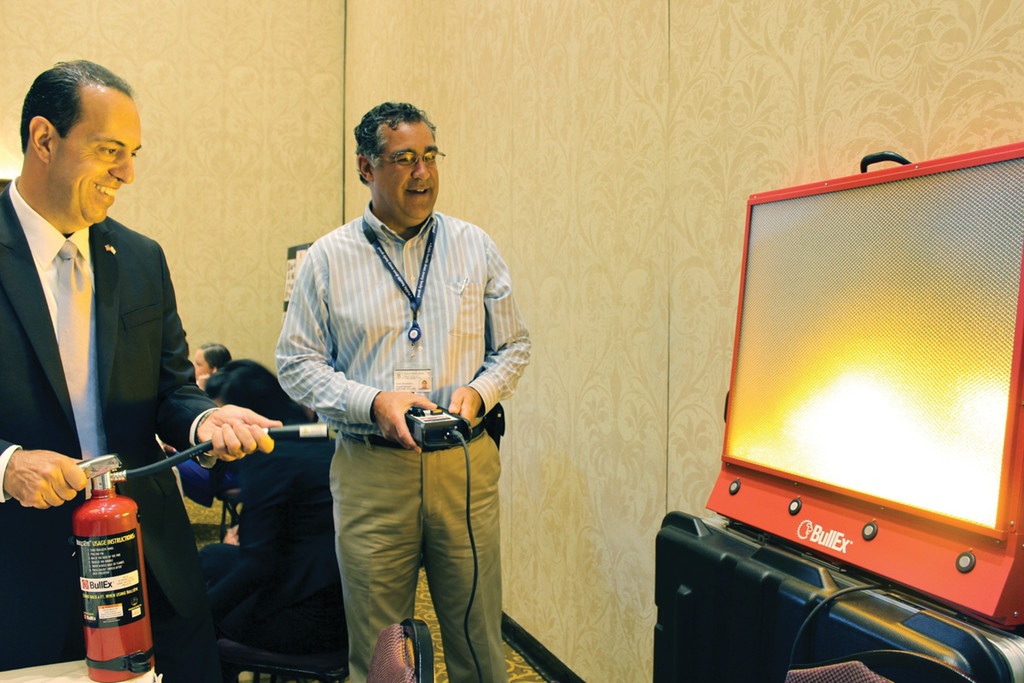 "FIRED UP ABOUT EXPO: Rhode Island's Secretary of State, A. Ralph Mollis, puts out a simulated fire during Tuesday's ""We Mean Business"" expo, an event that helped new and aspiring business owners with a chance to learn more about growing and starting successful companies. Jim Bruckshaw, program manager of the Occupational Safety and Health Administration, shows him how to operate the simulator."