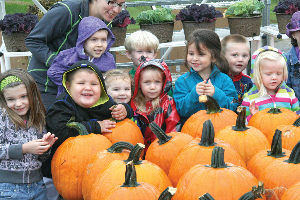 PUMPKIN FACES: Kids from The Learning Garden on Warwick Neck gather for a group shot behind the pumpkin display at Morris Farm.