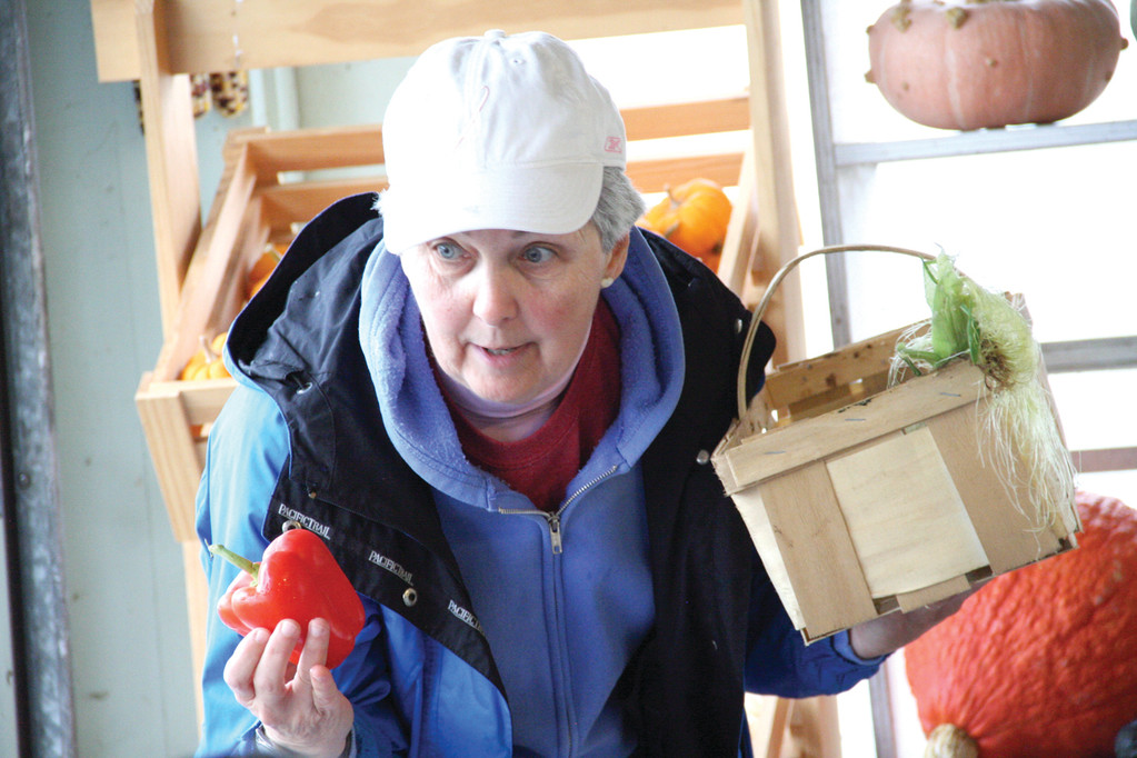 IT ONCE WAS GREEN: Retired teacher Cheryl Cotter, along with Cindy Morris, serves as a tour guide. Here Cotter holds a red pepper, which she said started off as a green pepper.