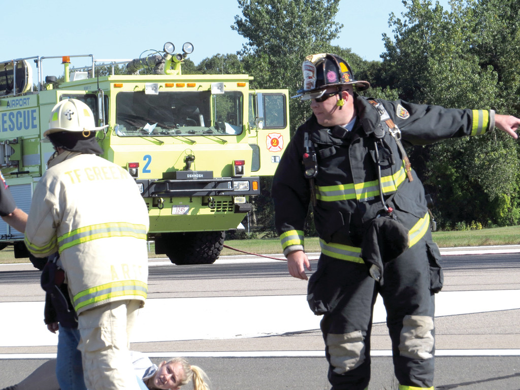 FIRST TO RESPOND: Members of T.F. Green�s RIAC Aircraft Rescue and Firefighters (ARFF) are first to the scene during Saturday morning�s Disaster Preparedness Drill.