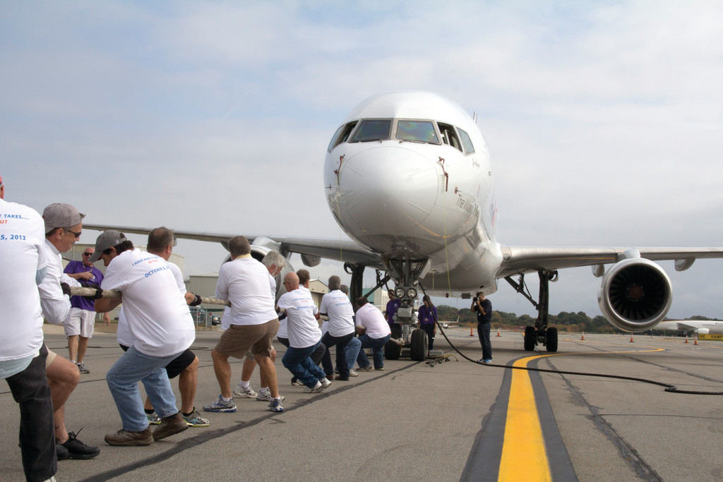 HOME (AIR)FIELD ADVANTAGE: Team FedEx gets a chance to tug their own plane down the tarmac for a good cause. FedEx donated the 160,000-pound Boeing 757 for the day, along with several members of their ground crew.