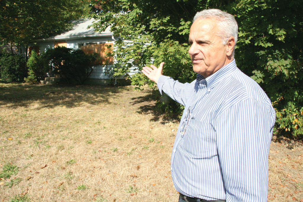 A DIFFERENT PICTURE: Ward 5 Councilman Edgar Ladouceur stands in front of the Park Avenue property that triggered his efforts to strengthen city laws regulating the upkeep of vacant property.