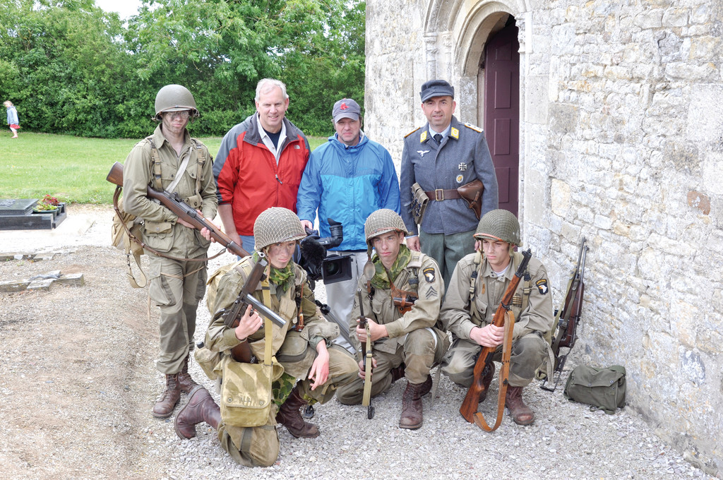 Filmakers Jim Karpeichik and Tim Gray (back row center) pose with some of the reenactors for their film, Eagles of Mercy, about two American medics who treated Allied and Gemran soldiers alike after D-Day in Normandy. They are standing outside the church they used as a medical station.
