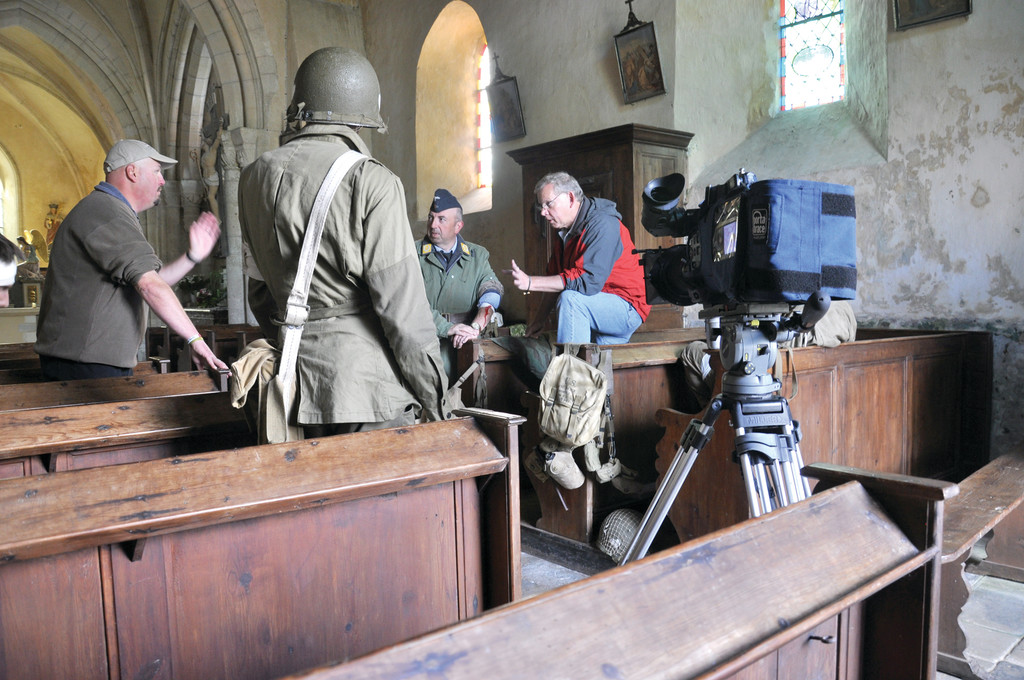 Filmmaker Jim Karpeichick consulted with historian and author Paul Woodadge (left) before filming for Eagles of Mercy in Angoville-au-Plain in Normandy. The church itself has stained glass windows honoring the two medics who saved lives on both sides of the battle for the village in WWII