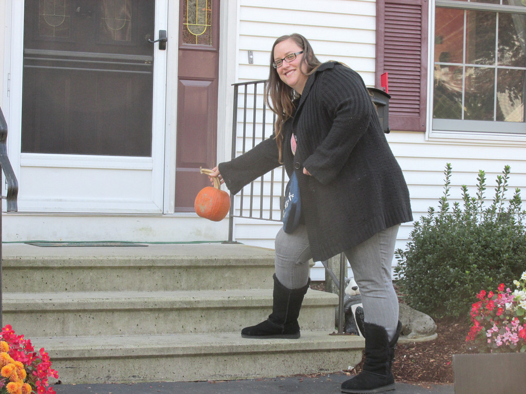 CAUGHT IN THE ACT: Aubrie Garofalo is all smiles as she places the first of 900 pumpkins on a doorstep at 12 Shenandoah Drive in Warwick that Slocum Realty distributed last weekend as the company