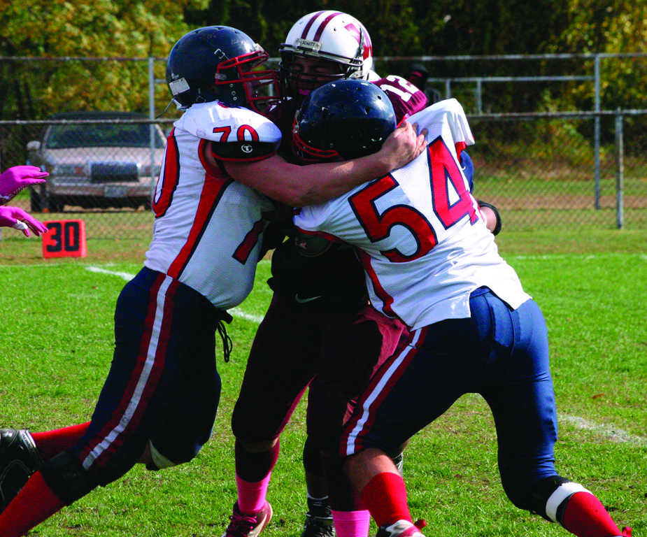 DOUBLE TROUBLE: James Marsella (70) and Nick Brown sandwich Woonsocket quarterback Miguel Raymond during the Titans 20-8 loss on Saturday.