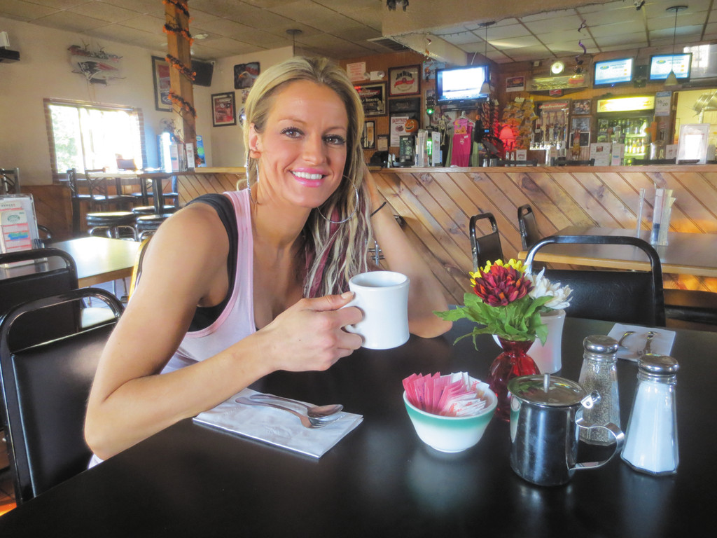 Bartender Kathleen raises a cup of coffee to announce Backstreet Bar and Grill's new breakfast menu-starting this weekend.