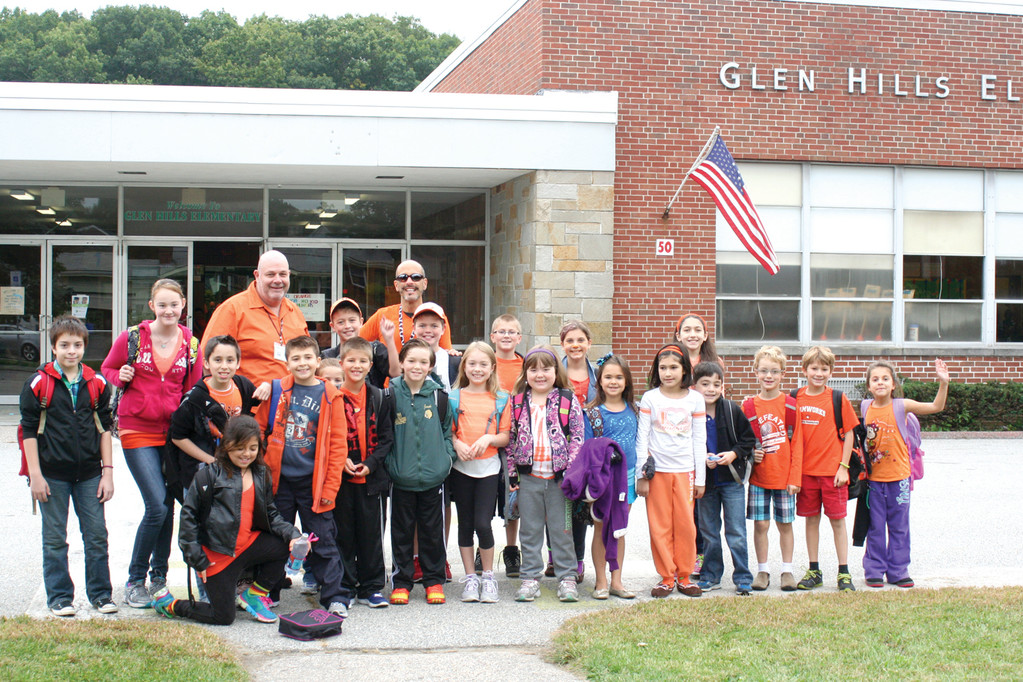 GOING ORANGE AT GLEN HILLS: Principal Jay DeCristofaro and art educator Paul Carpentier pose in front of the school with students heading into school on Go Orange Day.