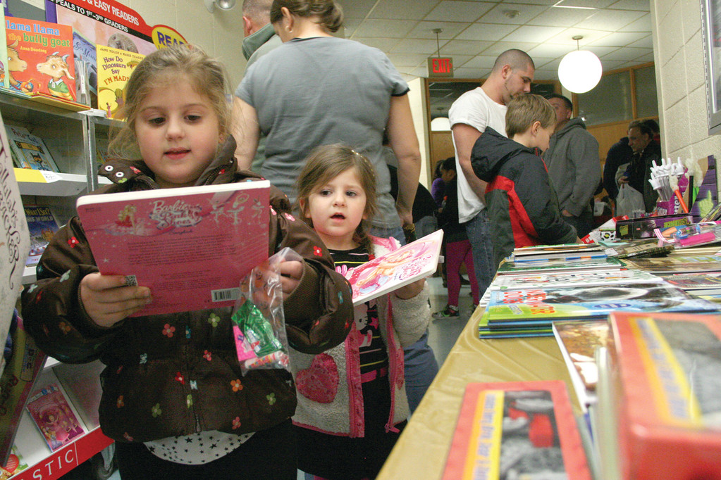 PICKING OUT BOOKS: First grader Olivia Bradford and her younger sister, Reese, look over the large book selection.