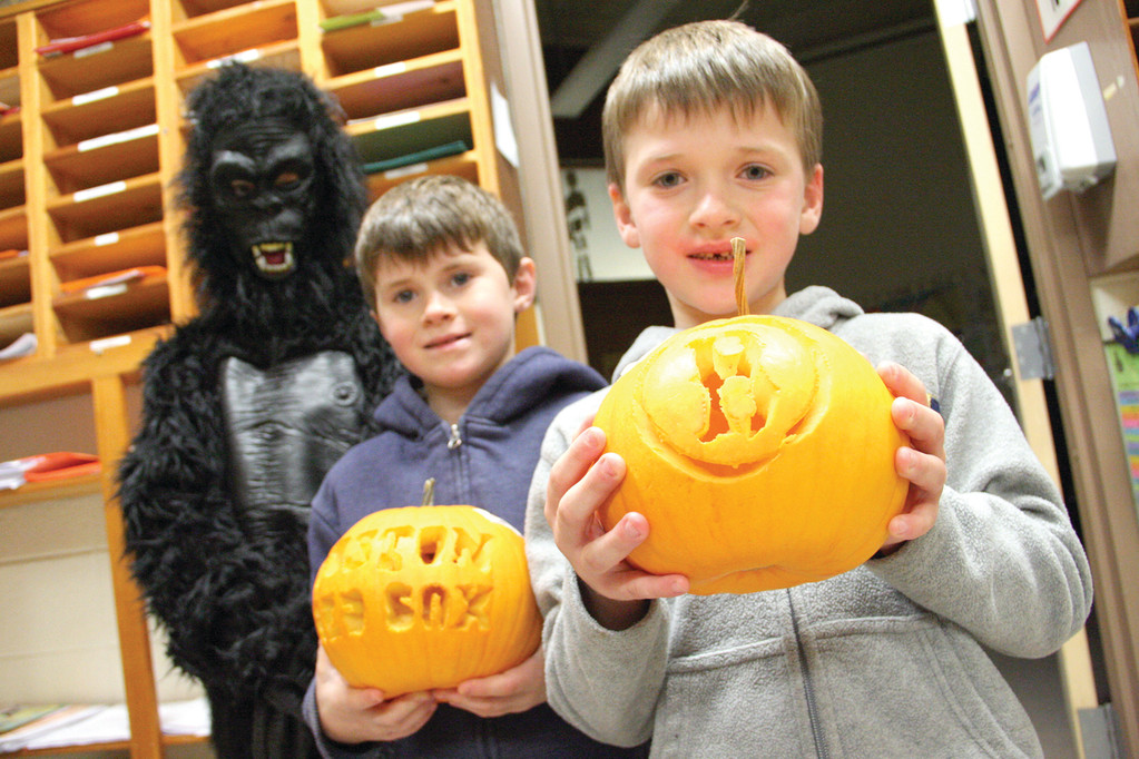 Here, the gorilla – 6th grader Matt Galipeau – looks over the Red Sox themed pumpkins carved by Ryan Hansen and his brother Jared. Jared's pumpkin was one of several winners.