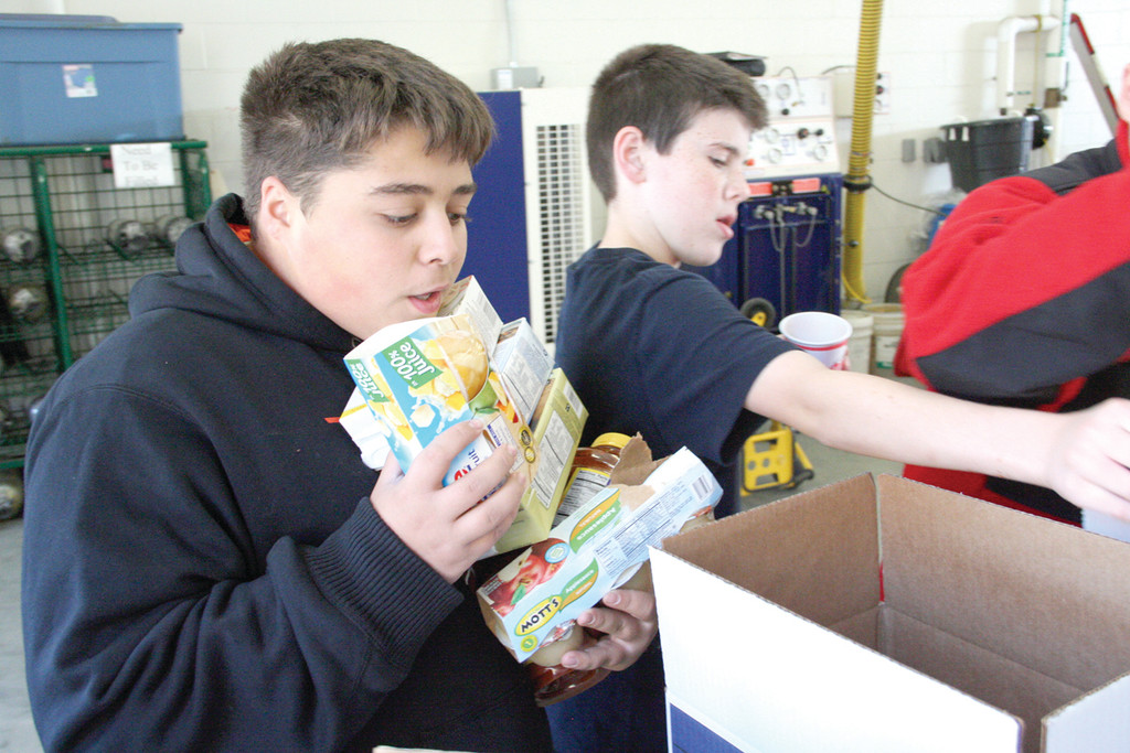 UP TO HIS CHIN: Conner Brennan of Troop 71 Cowesett collects boxes of soup to be separately boxed from canned foods and other donations at Fire Station 1 in Apponaug.