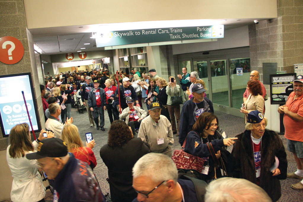 HONORING OUR VETS: Family, friends, fellow travelers and police and fire honor guards applauded and saluted the veterans as they entered the Sundlun Terminal at Green Airport.