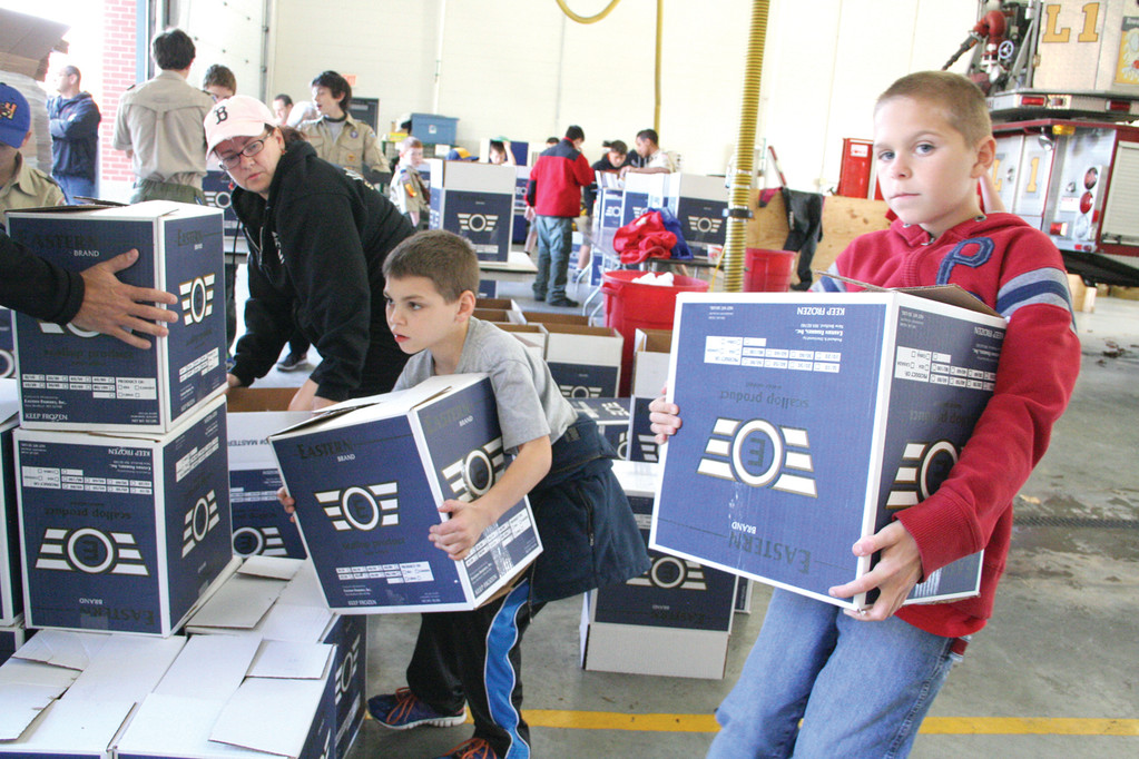 READY FOR PICKUP: Jimmy Burnham of Pack 71 and Michael Lewis of Troop 7, at left,  wrestle with completed boxes prior to a pickup from the Food Bank.