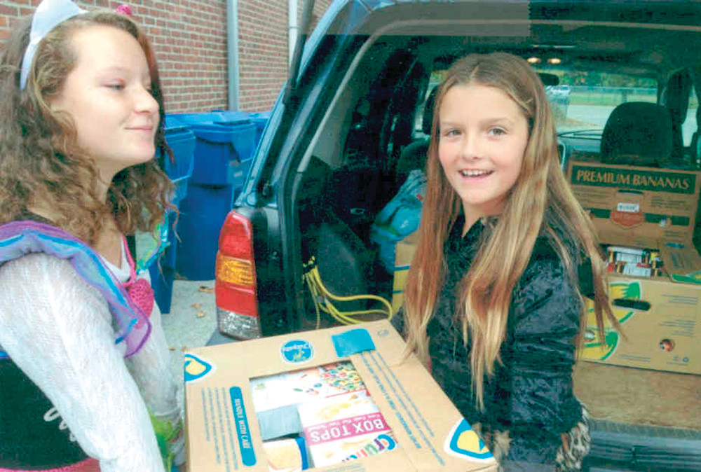LOAD IT UP: Giavanna Derby and Janessa Clements load a box of collected food items into the trunk of a van during the Oakland Beach Food Drive during Halloween week.