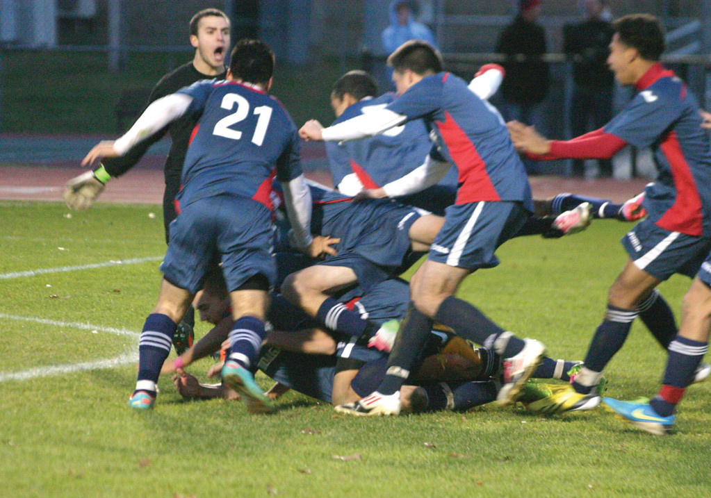 PILE ON: The Titans go wild after Zach Bromage's successful kick clinched the championship.