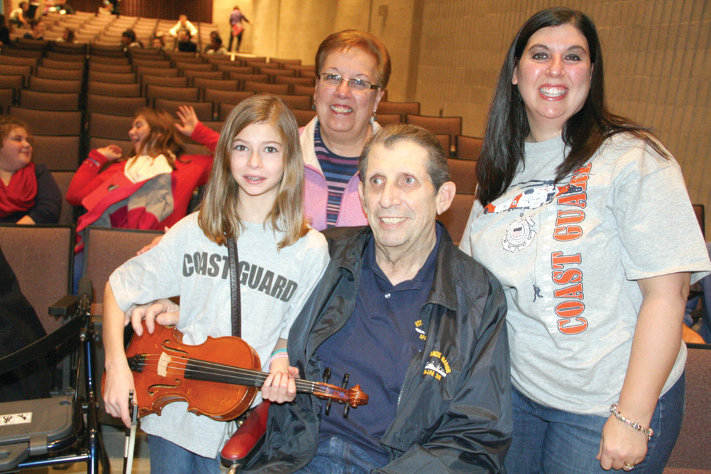 THEIR TOP VETERAN: Bob Sorgi, a Vietnam War veteran, is surrounded by his granddaughter Abigail Langevin; wife Maryann; and daughter Deb Langevin at the conclusion of the assembly.
