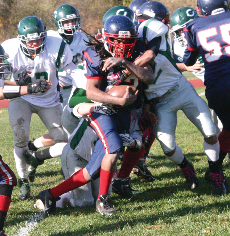 FULL STEAM: Chris Durand fights his way through Chariho tacklers on Saturday.