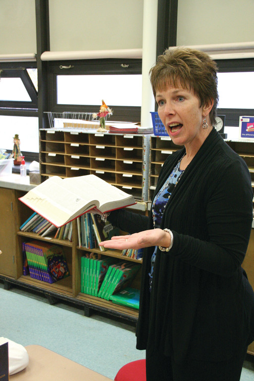 HER COLLEGE DICTIONARY: Robertson third grade teacher Tammy Ferguson shows the class the dictionary she has had since being a college student. She pointed out the dictionaries given to students Tuesday will serve good use for years to come.