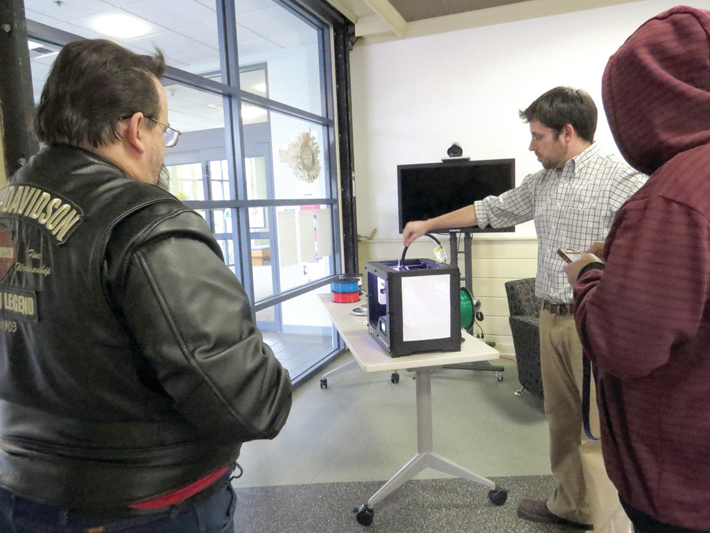 NEW 3D WORLD: Evan Barta, coordinator of technology for the Library, explains how the new 3D printer in the Idea Studio works to a few curious patrons.