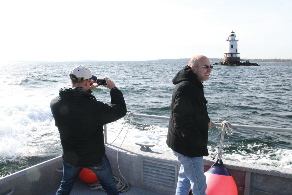 DESIGNS ON A LIGHT: Nick Korstad takes photos of Conimicut Light. Dave Tobin of Capitol Contracting joins him.