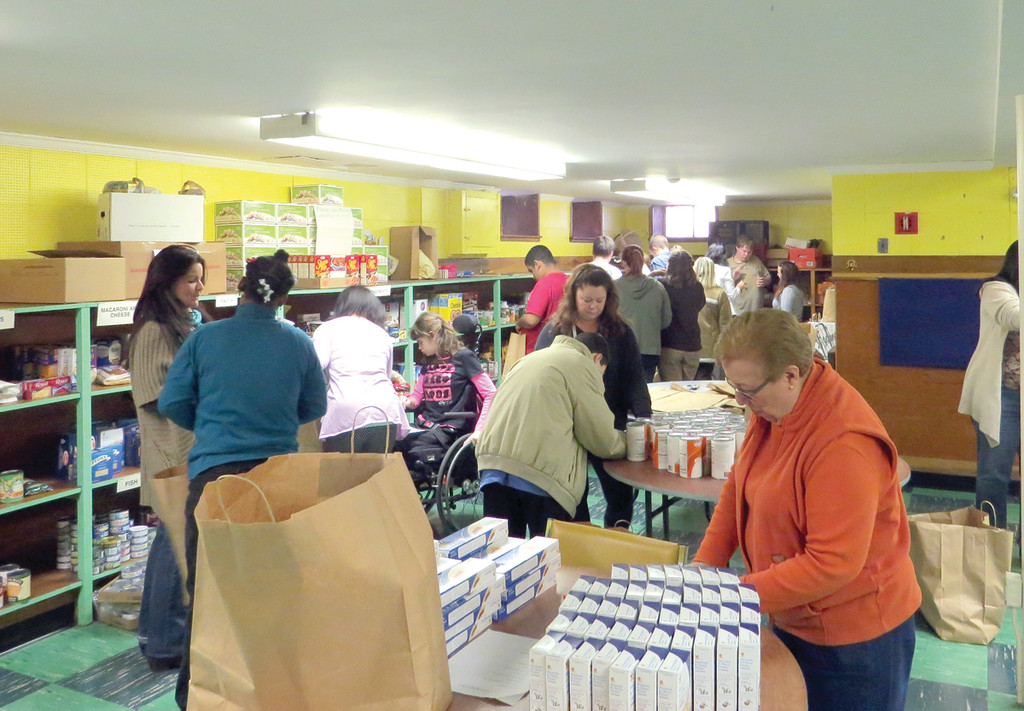 EVERYTHING BUT THE TURKEY: The students worked quickly and efficiently filling bags with donated food, traveling through St. Peter's Food Pantry with a checklist of food items families need for Thanksgiving, including corn, mixed vegetables, muffin mix, stuffing, gravy and more.