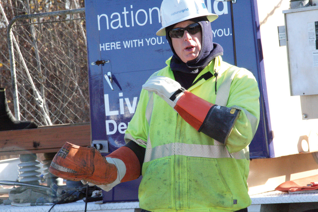 SHOES LIKE THIS: National Grid crew leader Michael Hannigan shows a properly insulated pair of rubber shoes.