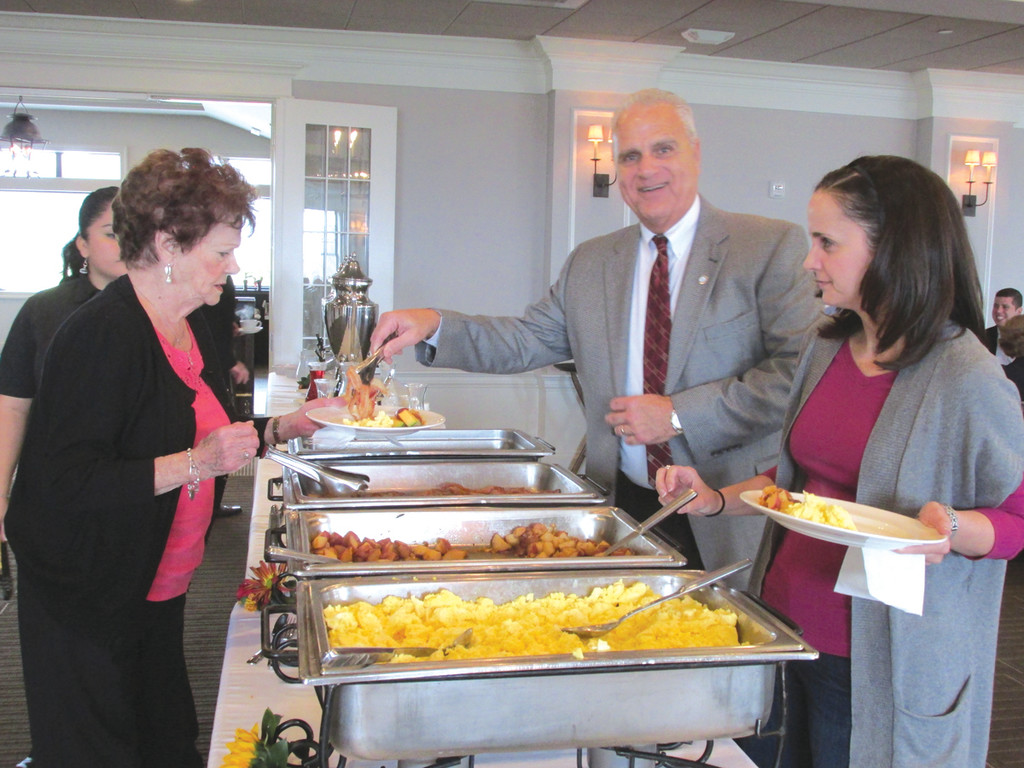 AT THEIR SERVICE: Ward 5 City Councilman Ed Ladouceur (top right) serves his mother Cecile Ladouceur during Sunday�s special fundraiser at Harbor Lights Country Club and Marina, as his daughter Julie Ladouceur awaits the same service. More than 100 people turned out in support of the first-term councilman.