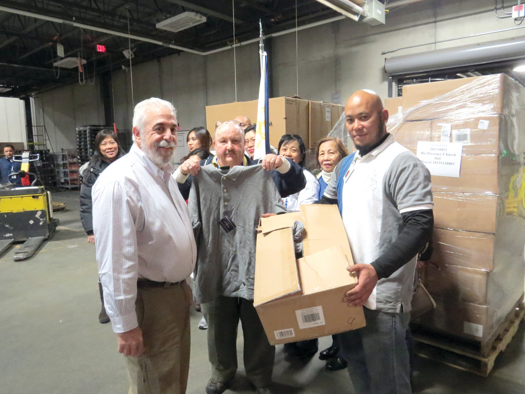 CLOTHING: Ocean State Job Lot founder and owner Alan Perlman, Dan Aurelio and a member of His Presence Church show off just one of the 30,000 pieces of clothing being sent to a sister network of churches in the Philippines for typhoon relief efforts.