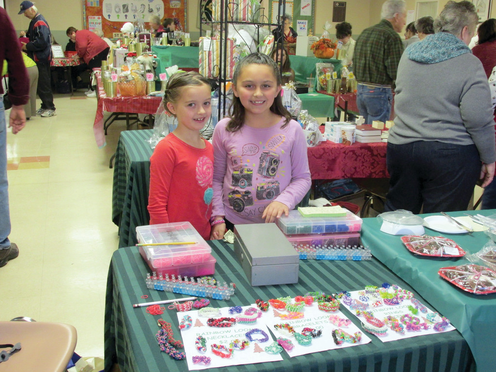 STRAIGHT FROM THE LOOM: While their mom worked in the Schweitzer Hall Café, Sofia Teolis (left), 7, and her sister Mackenzie, 9, hold unique Rainbow Loom items they made from scratch.