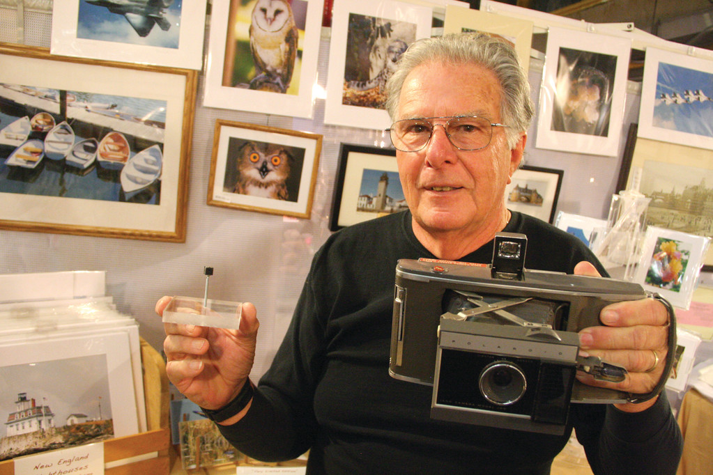 INSTANT PHOTOS: Richard Hopkins said he loves participating in the crafts festival as he gets to meet and talk with so many interesting people. Hopkins, who takes pictures as a hobby � he particularly enjoys photographing animals � offered a bit of history in his display. Here, he displays a Polaroid camera, which was the innovation of its time, and the camera from a cell phone to illustrate how instant photography has changed in a few short decades.