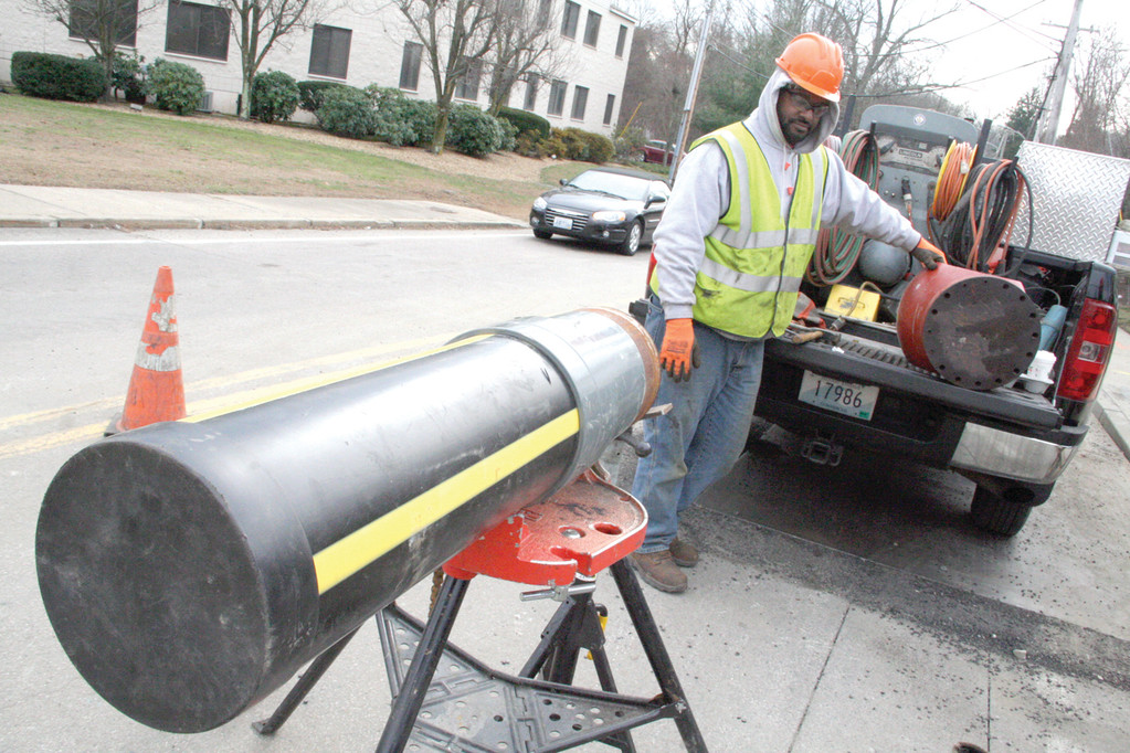 THE NEW PIPE: A section of eight-inch plastic pipe, which will replace steel and cast iron gas pipes in Diamond Hill Road, is readied for a connection to a 12-inch main in Centerville Road.