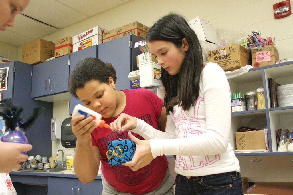 COOPERATIVE CREATION: Hoxsie School fifth graders Macenzie Bryant and Elizabeth Benoit work on their ornament.