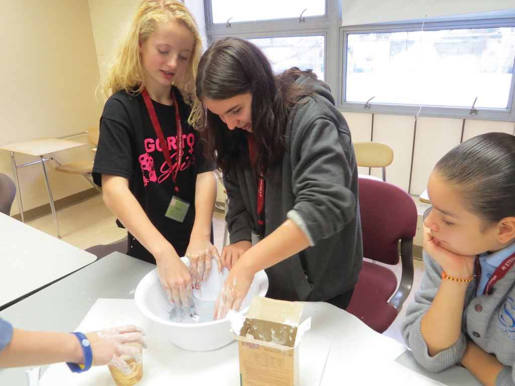 "HANDS-ON SCIENCE: Gorton seventh grader Madison Foster (far left), along with students from John F. Deering Middle School in West Warwick and Sophia Academy in Providence, experiments with ""oobleck."" Foster described the substance as similar to quicksand – if she tossed it between her hands quickly, it was a solid, but if she tried to hold it in one hand, it was a liquid."