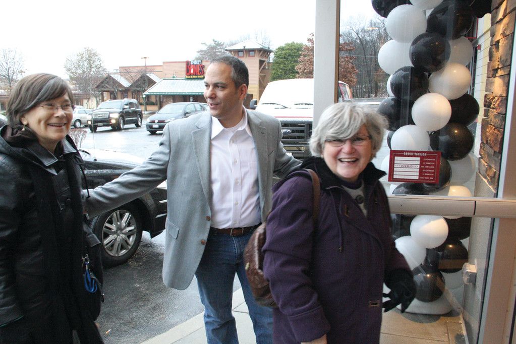 FIRST PATRONS: Glenn Beattie welcomes patrons to the Corner Bakery Café that opened yesterday on Route 2.