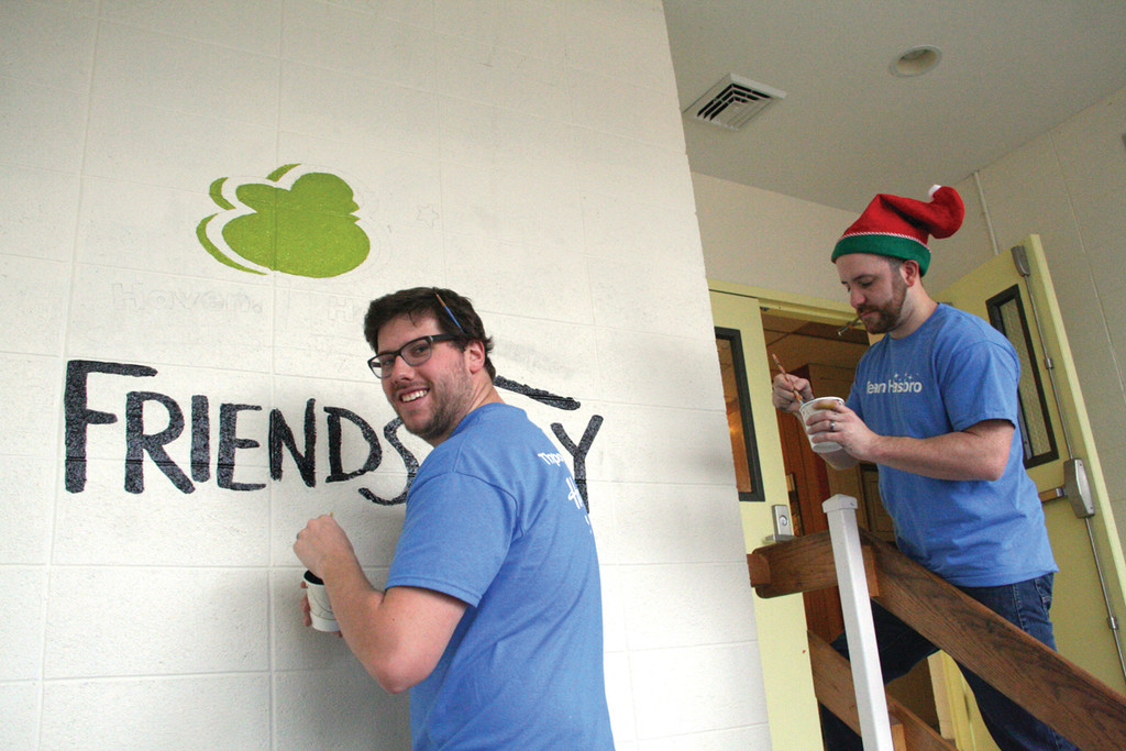 NO MISTAKING WHERE THEY ARE: Hasbro team members Sam Smith and Joseph Grasso work on the entryway to Friends Way.