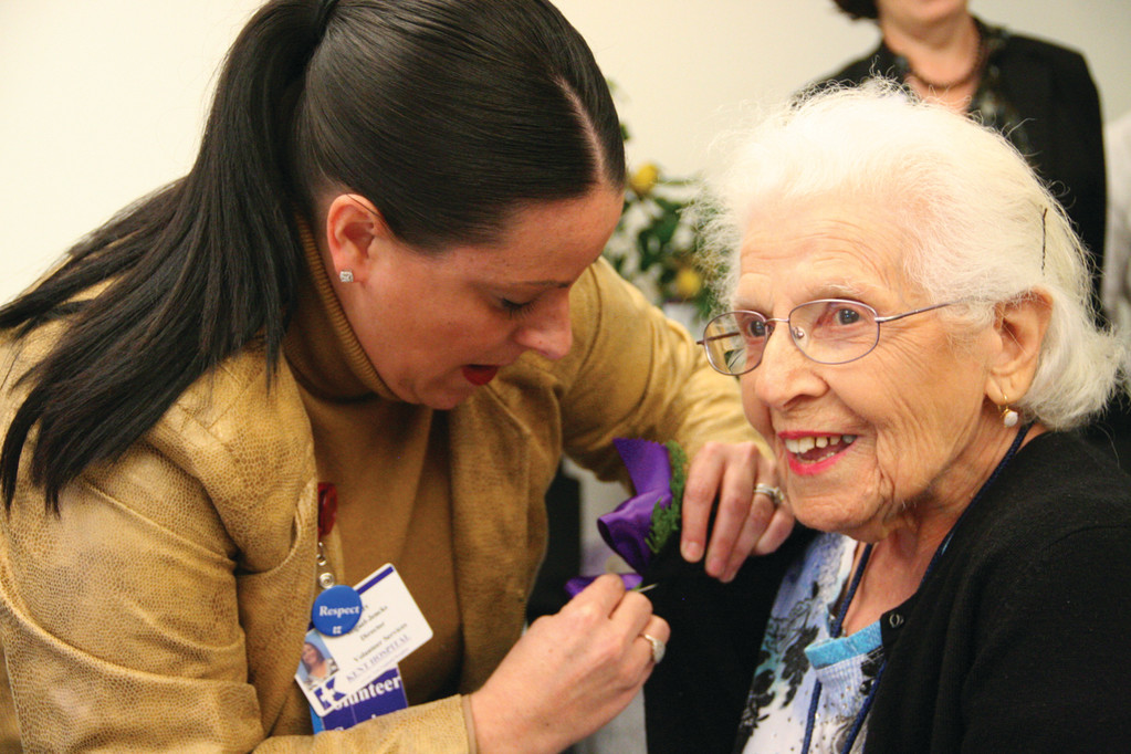 WOMAN OF THE HOUR: Jody Jencks, director of hospital volunteer services, pins a corsage on Mary Poncin, who was feted Tuesday on her 100th birthday. Mary works as a greeter at the hospital.
