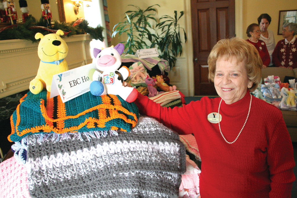 GIVING BACK: Soon after starting the Y knitting club 13 years ago, Georgia McDermott initiated knitting to fulfill the requests of 13 non-profit agencies. Here she is beside those items that went to the Elizabeth Buffum Chace Center.